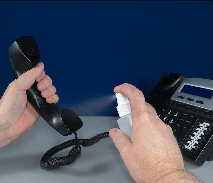 hands spraying a liquid on a black office phone