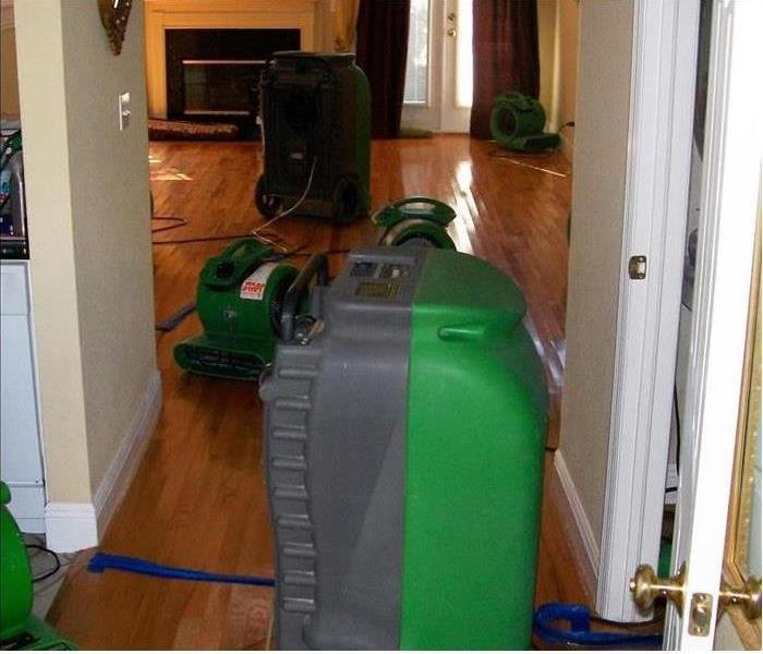 large industrial-grade dehumidifiers and air movers removing moisture from hardwood floors